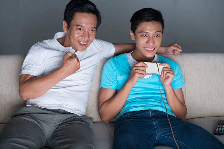 A father supporting his son playing video game