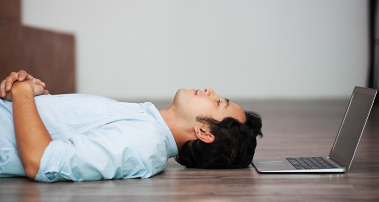 man lying on floor at his laptop