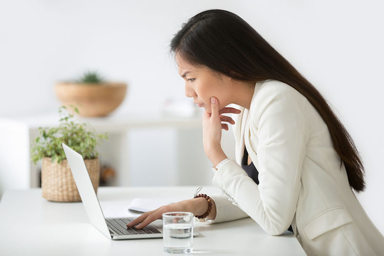 Asian woman concentrating hard looking at laptop screen