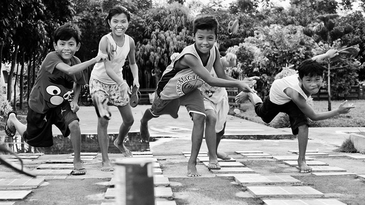 Pinoy kids playing tumbang preso with their improvised toys (slippers and tin can)