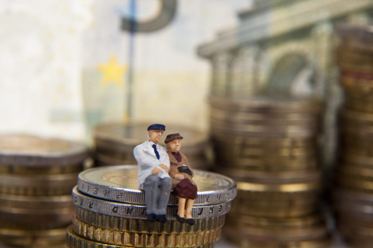 Elderly couple figurine placed on stacks of coins