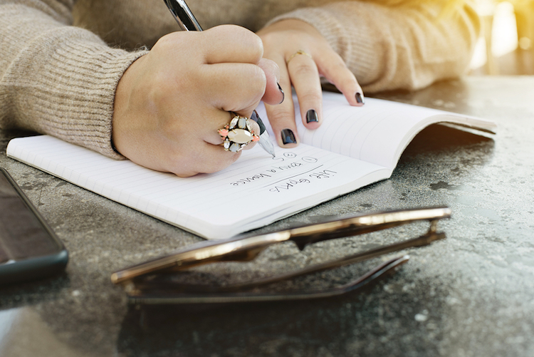 View Of Female Hands Writing Her Life Goals In A Journal